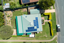 Looking Down On House With Metal Roof And Solar Panels.