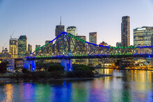 Colourful Lights From A Large Bridge And City Skyline Reflected In A River At Sunset