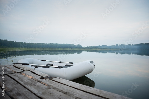 Carta da parati Inflatable boat on the lake water background near the old wooden pier