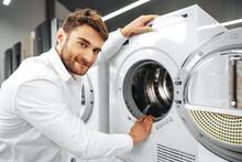 Young Man Choosing New Washing Machine In Household Appliances Store