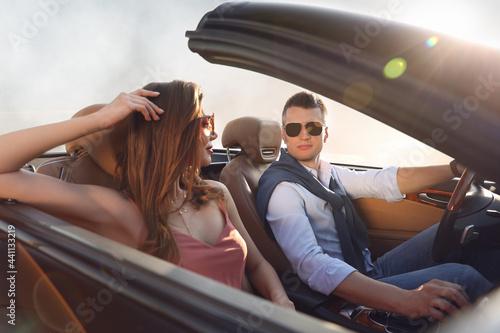 Fototapeta Stylish couple driving luxury convertible car outdoors