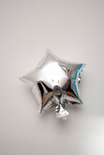 Silver Star Shaped Balloon Hanging On The Wall Isolated On White