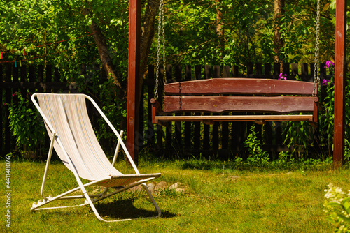 Garden with deck chair and swing Fotobehang