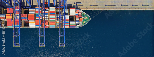 Aerial top down ultra wide photo of industrial container ship loading  - unloading colourful truck size containers with cranes in logistics terminal port