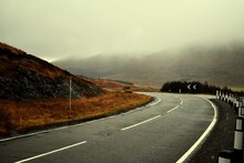 Road By Mountains Against Sky During Foggy Weather