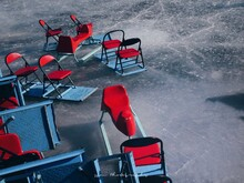High Angle View Of Empty Chairs On Frozen Lake During Winter