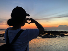 Silhouette Of A Young Woman Making Heart Love Sign Against Colorful Sunset On The Beach.