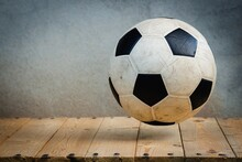 Close-up Of Soccer Ball On Table Against Wall