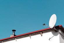 Satellite Dish On A Roof. And Blue Sky.