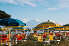 Chairs And Umbrellas On Beach Against Sky