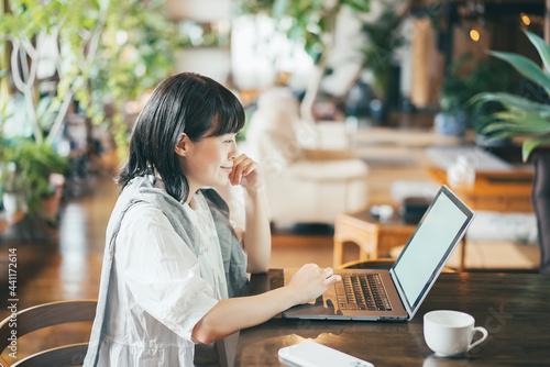 Slika na platnu 暖かい雰囲気の空間で、ノートパソコンの画面を見る女性