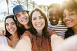 Group of happy multiracial people taking a selfie with mobile phone with back sunlight - Multiethnic friends in summer clothes having fun on holidays - Friendship and summer vacation concept