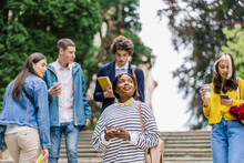 Positive Brooding Attractive African American Female Student Thinking And Looking Upward Standing On Stairs While People, Fellow Students Are Walking Around Her.