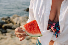 Mid Section Of Woman Holding Piece Of Watermelon On Beach.