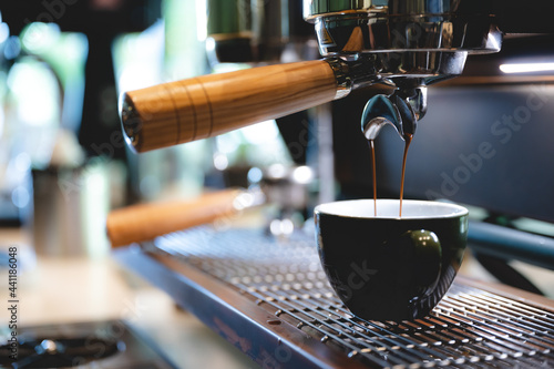 Fototapeta professional barista making espresso coffee to a drink cup in cafe, beverage caf