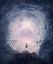 Person Stands On The Edge Of A Cliff Above A Waterfall Looking At A Huge Whirlwind In The Clouds That Creates A Portal To Another Planet. Surreal And Fantasy Scene, Magical World Adventure Concept
