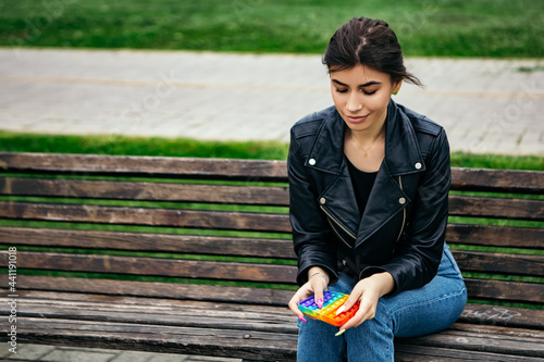 Obraz na plátně Simple dimple colorful anti stress pop it woman hold hand popping game