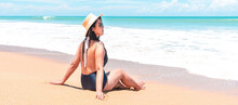 Back View Of Asian Traveler Woman In Swimsuit And Straw Hat To Sitting In The Spray Of The Sea To Looking View