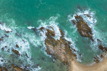 Aerial Top View Of White Waves In Green Sea Hit On The Large Rocks In Summer Day. .Beach Sea Space Area. Green Sea, Waves Crashing On The Rocks.. At Kalim Beach Phuket Thailand.