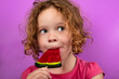 Leinwandbild Motiv child enjoying watermelon lollipop, pretty little girl licking candy