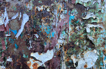 The Texture Of A Rusty Metal Wall Surface With Paint Residues And Scraps From Ads