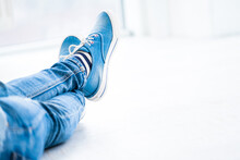 Crossed Legs Wearing Gumshoes On White Background
