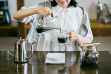 おしゃれな空間で、コーヒーを淹れる若い女性