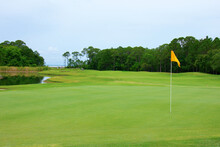 Lush Golf Course Green With Yellow Flag In The Hole And Fairway With Water Trap, Sand Traps And Tree Line In Central Florida On A Crisp Summer Morning.