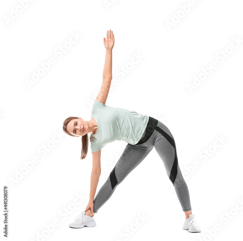 Fotografija Sporty young woman training against white background