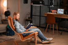 Young Man Reading Book While Sitting In Armchair At Home