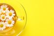 Leinwandbild Motiv Cup of tasty chamomile tea with flowers on color background, closeup