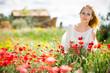 Leinwandbild Motiv Beautiful woman wearing white dress in poppy field and enjoying summer day
