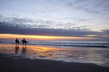 Horse Riders On A Beach At Sunrise