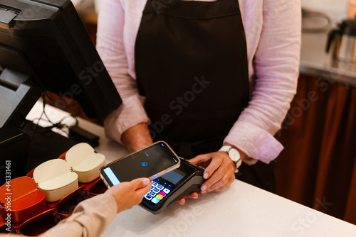 Fotografie, Obraz Woman wearing face mask working with payment terminal at cash register