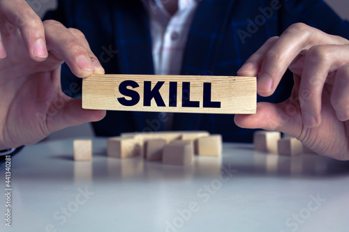 Fototapeta Businessman hand holding wooden cube block with SKILL business word on table background