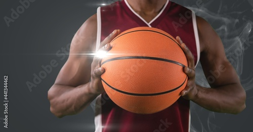Mid section of male basketball player holding ball against smoke and light spot on grey background