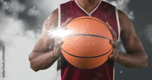 Mid section of male basketball player holding basketball against light spot on grey background