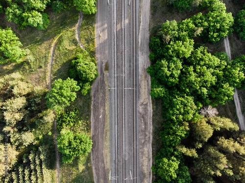 Billede på lærred Aerial view of railroad in sunny summer day in forest
