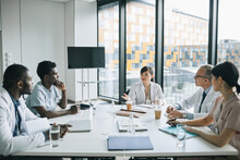 Wide Angle View At Diverse Group Of Doctors Sitting At Meeting Table In Conference Room During Medical Seminar, Copy Space