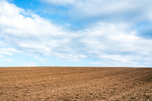 Plowed Brown Field And White Clouds On Blue Sky.cloudy Sky Over Brown Field.Spring Summer Day.