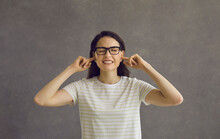 I Can't Hear You. Head Shot Of Young Woman In Glasses Closing Eyes And Plugging Ears With Fingers To Ignore Loud Noise, Unwanted Opinion, Dumb Stupid Comment Or Useless Unsolicited Uninvited Criticism