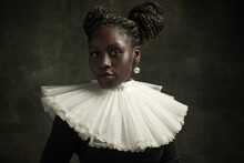 Close-up Portrait Of Medieval African Young Woman In Black Vintage Dress With Big White Collar Posing Isolated On Dark Green Background.