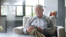 Senior Man Using Digital Tablet Sitting On The Couch At Home
