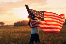 Woman Farmer In Wheat Field Waving American Flag On Sunset.