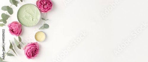 tender flatlay composition with balm for lips, flowers on white background. Concept beauty natural vitamin cosmetic product, skin body care, top view, copyspace, banner