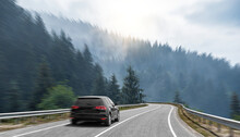 A Black Car Rushes Along The Road Against The Backdrop Of A Beautiful Landscape.
