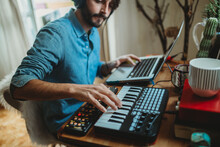 Musician Using Synthesizer And Laptop At Home