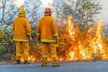 Two Firemen Watching Over A Roadside Fire
