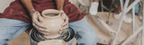 partial view of young african american man making wet clay pot on wheel in pottery, banner