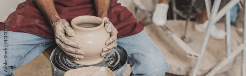 Fotografija partial view of young african american man making wet clay pot on wheel in potte
